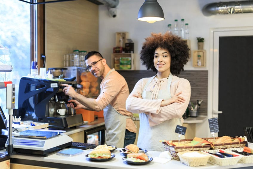 Couple coworkers standing arms crossed in fast food restaurant.